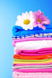 Stapel der bunten Kleidung und der Blumen Stockbilder
