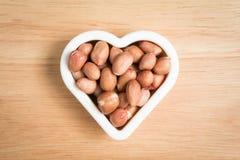 Stapel der Erdnuss in einem Herzformstein Lizenzfreie Stockbilder