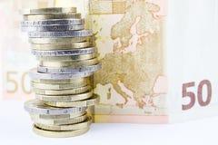 Stapel der Euromünzen und der Banknote Stockfotos