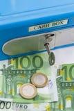 Stapel der Euromünzen und der Banknoten in einem Bargeldkasten Stockfotografie