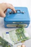 Stapel der Euromünzen und der Banknoten in einem Bargeldkasten Lizenzfreies Stockfoto