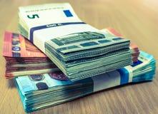Stapel der Eurorechnungen auf einem Kiefernschreibtisch in fives, zehn und Zwanziger Jahre Stockbild