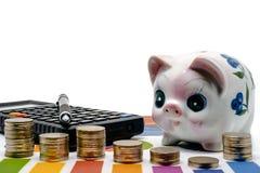 Stapel der Geldmünze auf Balkendiagramm mit Sparschwein, Taschenrechner und Lizenzfreie Stockfotografie