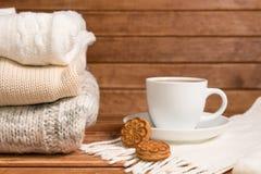 Stapel der gemütlichen gestrickten warmen Strickjacke, hölzerner Hintergrund strickjacke Stockfoto
