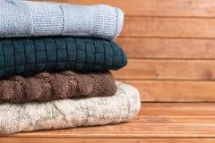 Stapel der gemütlichen gestrickten warmen Strickjacke, hölzerner Hintergrund strickjacken Stockfotografie