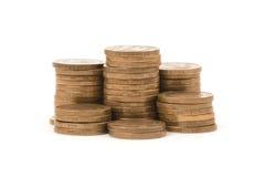 Stapel der goldenen Münzen getrennt auf einem weißen Hintergrund Lizenzfreie Stockfotos