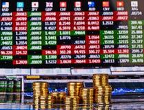 Stapel der goldenen Münzen und das Finanzdiagramm als Hintergrund. Stockbild