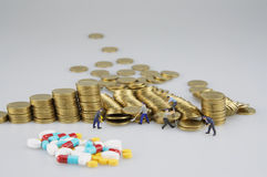 Stapel der Goldmünze mit Miniaturleute- und Unschärfemedizin stockfotografie