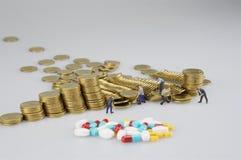 Stapel der Goldmünze mit Miniaturleuten und Medizin lizenzfreies stockbild