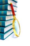 Stapel der grünen Bücher und des Vergrößerungsglases Stockbilder