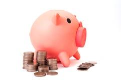 Stapel der Münze und der piggy Querneigung Stockfotografie