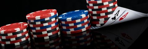 Stapel der mehrfarbigen Pokerchips und zwei Spielkarten auf einem schwarzen Hintergrund, langes Foto stockfoto