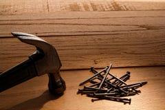 Stapel der Nägel und des Greifer-Hammers auf hölzernen Vorständen Stockbilder