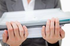 Stapel der Schreibarbeit, die durch weibliche Hände angehalten wird lizenzfreies stockbild