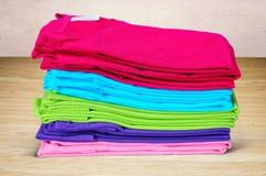 Stapel der T-Shirts der mehrfarbigen Frauen auf hölzernem Hintergrund Stockfotografie