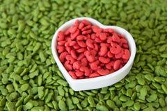 Stapel der trockenen Nahrung für Haustiere mit roter Farbe in der Herzschale, Liebeshaustierkonzept Stockfotografie
