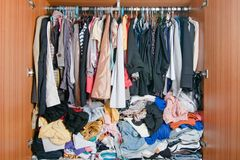 Stapel der unordentlichen Kleidung im Wandschrank Unordentliche durcheinandergeworfene Frauengarderobe stockfotografie