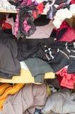 Stapel der unvorsichtig zerstreuten Kleidung in der Garderobe stockfoto