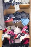 Stapel der unvorsichtig zerstreuten Kleidung in der Garderobe lizenzfreie stockfotografie