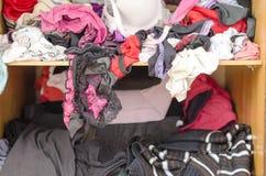 Stapel der unvorsichtig zerstreuten Kleidung in der Garderobe stockbilder