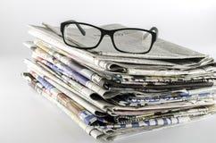 Stapel der Zeitung mit Gläsern Lizenzfreie Stockfotos