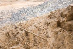 Stapel des Bausandes und -kieses mit Spaten stockbild