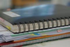 Stapel des Berichts und des schwarzen Notizbuches stockfotografie