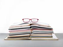 Stapel des Buches und der roten Gläser Stockbilder