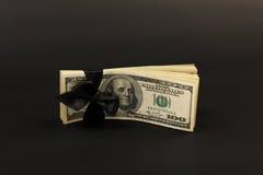 Stapel des Geldamerikaners hundert Dollarscheine mit schwarzem Bogen auf schwarzem Hintergrund Lizenzfreie Stockfotos