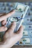 Stapel des Geldes in der Hand auf einem weißen Hintergrund Stockfotografie