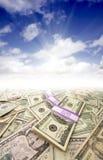 Stapel des Geldes, des Sonnendurchbruchs und des blauen Himmels stockbild