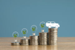 Stapel des Geldes prägt mit Auto des kleinen grünen Baums, der Glühlampe und des Papiers auf hölzernem und weich Blau Lizenzfreies Stockfoto