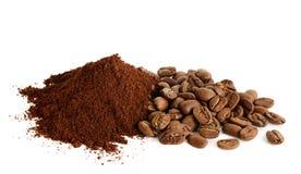 Stapel des gemahlenen Kaffees und der Kaffeebohnen auf weißem Hintergrund Stockfotos