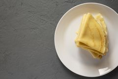 Stapel des geschmackvollen Blini auf einer wei?en Platte ?ber konkretem Hintergrund Flache Lage, obenliegend, von oben Kopieren S lizenzfreies stockbild