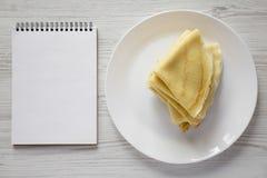 Stapel des geschmackvollen Blini auf einer wei?en Platte, leerer Notizblock ?ber wei?em h?lzernem Hintergrund, Draufsicht Flache  stockfotos