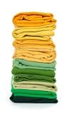 Stapel des Grüns und der Gelb gefalteten Kleidung Lizenzfreie Stockfotografie