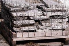 Stapel des Granitdias bessert in ein Metallnetz aus Stockfoto