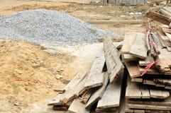 Stapel des Holzes und des Kieses in einer Baustelle. Stockbilder