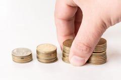 Stapel des Metalls prägt über weißem Hintergrund und der Hand, die Stapel von Münzen hält Stockbild
