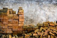 Stapel des roten Backsteins nahe Betonmauer Lizenzfreies Stockbild