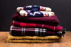 Stapel des warmen und gemütlichen Winters und des Herbstes kleidet auf hölzernen Hintergrund Strickjackenwolljacken-Schalhandschu Lizenzfreie Stockfotos