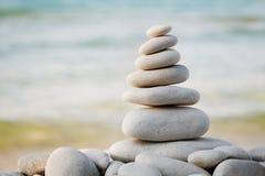 Stapel des weißen Kieselsteins gegen Seehintergrund für Badekurort-, Balancen-, Meditations- und Zenthema stockfotografie