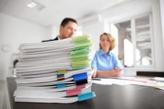 Stapel Dokumente auf Tabelle und unscharfen Arbeitskräften stockfotografie