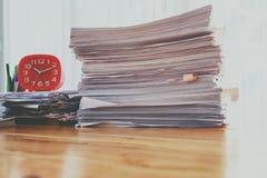 Stapel Dokumente mit roter Uhr und Büroartikel auf Schreibtisch im Innenministerium stockfotos