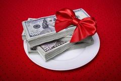 Stapel Dollar mit rotem Bogen auf einer Platte Lizenzfreie Stockfotografie