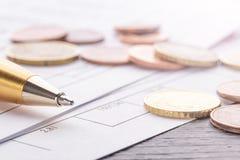 Stapel Euroeuromünzen auf altem schwarzem Holztisch Stift- und Buchhaltungsdokumente mit Zahlen stockfotografie