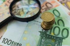 Stapel Euromünzen auf Stapel von Banknoten mit Lupe a Stockfotos