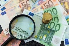 Stapel Euromünzen auf Stapel von Banknoten mit Lupe a Stockfotografie
