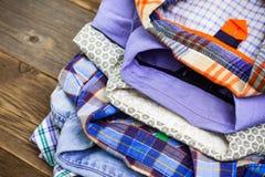 Stapel farbige Baumwollhemden auf einem hölzernen Regal Stockfotografie