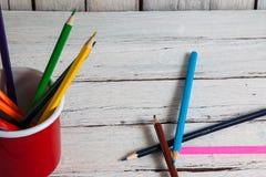 Stapel farbige Bleistifte in einem Glas auf hölzernem Hintergrund Stockfotos
